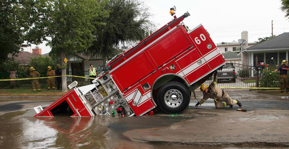 . A Los Angeles fireman looks under a fire truck stuck in a sinkhole in the Valley Village neighborhood of Los Angeles, in this Sept. 8, 2009 file photo. Four firefighters escaped injury early Tuesday after their fire engine sunk into a large hole caused by a burst water main in the San Fernando Valley, authorities said.  (AP Photo/Nick Ut, File)