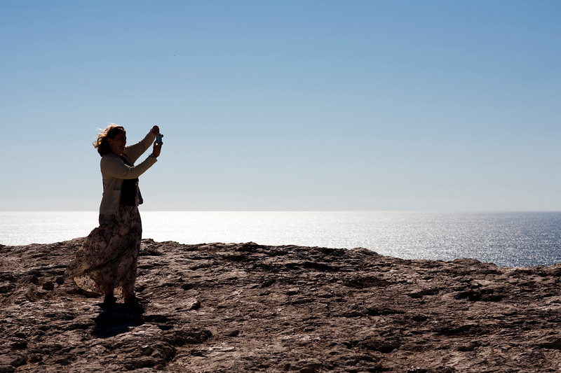Woman taking pictures at cabo Sao Vicente (Cape Saint Vincent), town of Sagres, municipality of Vila do Bispo, district of Faro, region of Algarve, southwestern Portugal