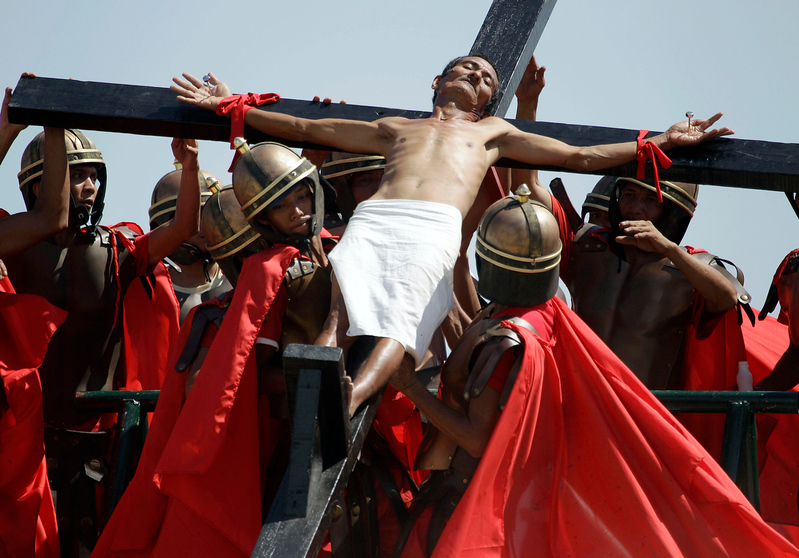. A Filipino penitent who is nailed to a wooden cross is raised by actors portraying Roman soldiers during Good Friday rituals on March 29, 2013 at Cutud, Pampanga province, northern Philippines. Several Filipino devotees had themselves nailed to crosses Friday to remember Jesus Christ\'s suffering and death, an annual rite rejected by church leaders in this predominantly Roman Catholic country. (AP Photo/Aaron Favila)