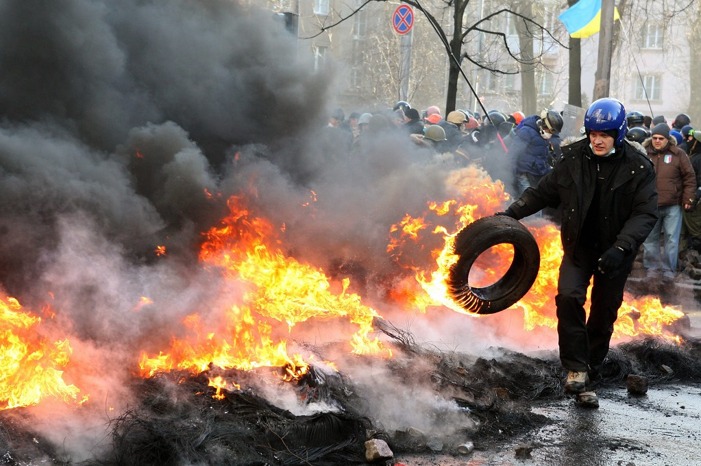 . An anti-government protester throws a tire in a barricade on the streets of downtown Kiev, Ukraine, 18 February 2014. A least three protesters were killed in clashes with police on 18 February, Ukrainian opposition activists say. EPA/IGOR KOVALENKO