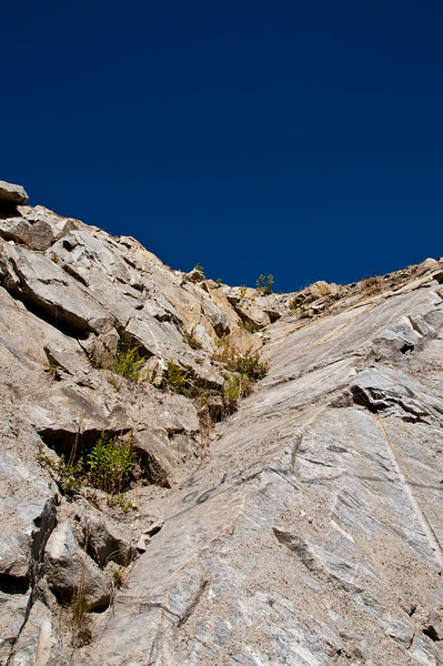 Looking up a rock face at a very clear blue sky.