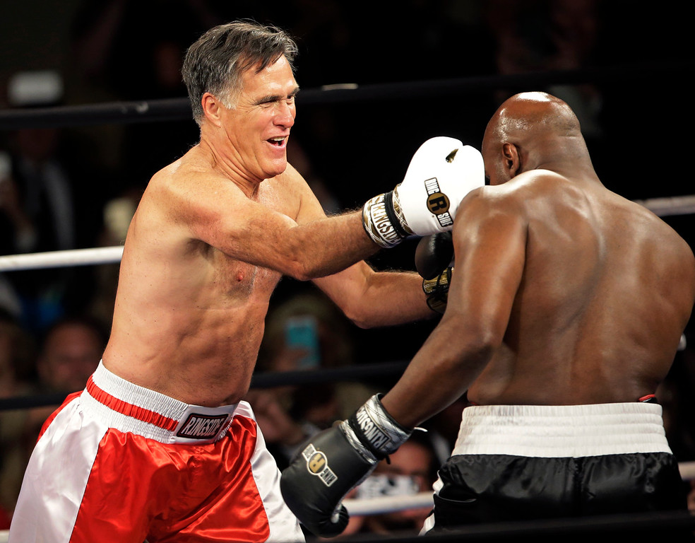 . Former Republican presidential candidate Mitt Romney, left, lands a punch against five-time heavyweight boxing champion Evander Holyfield at a charity fight night event Friday, May 15, 2015, in Salt Lake City. The black-tie event will raise money for the Utah-based organization CharityVision, which helps doctors in developing countries perform surgeries to restore vision in people with curable blindness. (AP Photo/Rick Bowmer)