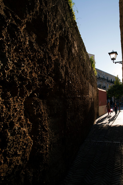 People walking by the medieval city walls, Seville, Spain