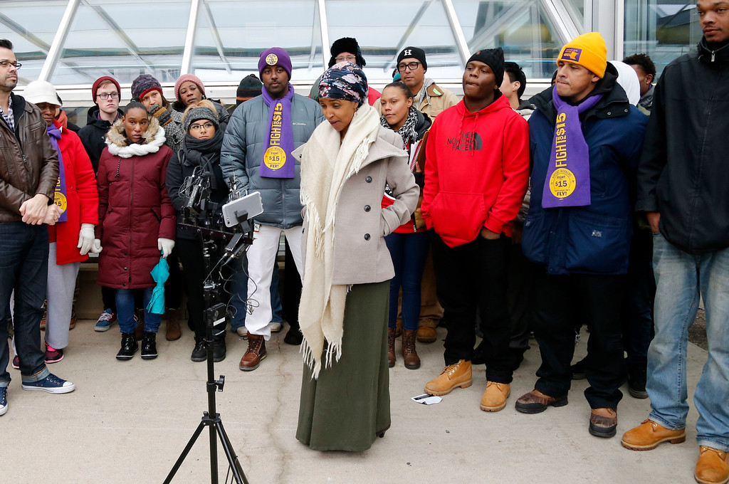 . Ilhan Omar, center, the first Somali-American elected to a state legislature, speaks during a rally Tuesday, Nov. 29, 2016, at the Minneapolis-St. Paul International Airport in Minneapolis calling for $15 minimum wages. Those in attendance included airport workers. (AP Photo/Jim Mone)