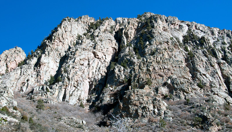 North end west Whiskey Peak. Summit ridge behind visible crest. Named 3 buttresses on face. North Buttress up left side right of low point with pinkish patch, Middle Buttress between 2 clefts, South Buttress right of right cleft.