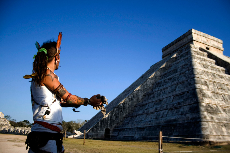 . In this March 20, 2010 file photo, a man performs a ritual as he looks toward the descent of the Kukulkcan serpent, whose image is seen illuminated along the edge of the stairs of the Mayan Chichen Itza pyramid, during the Spring equinox in Chichen Itza, Mexico. A chorus of books and movies tried to link the Mayan calendar to rumors of impending disasters ranging from rogue black holes and sun-storms to the idea that the Earth\'s magnetic field  could \'flip\' on that date. Archaeologists says there is no evidence the Maya ever made any such prophesy. (AP Photo/Israel Leal, File)