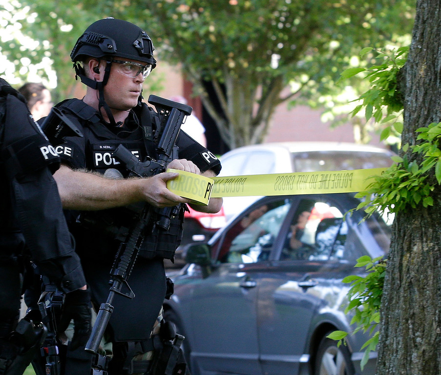 . A Seattle Police SWAT team officer strings police tape at the scene of a shooting, Thursday, June 5, 2014, at Seattle Pacific University in Seattle. (AP Photo/Ted S. Warren)