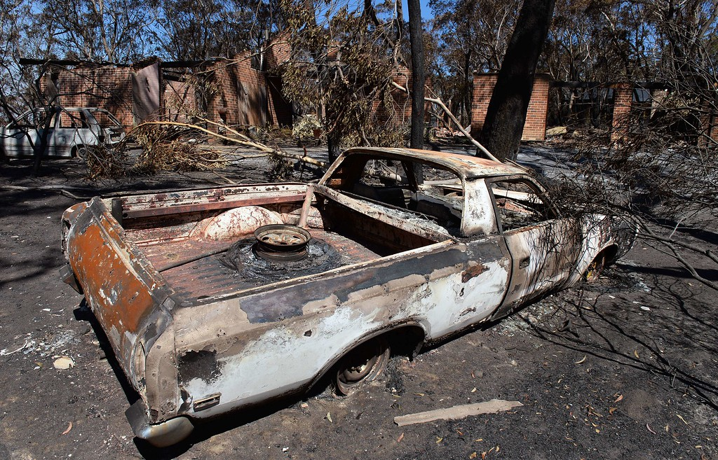 """. Burnt out cars sit in front of a destroyed house in Mount Victoria in the Blue Mountains on October 21, 2013, as volunteer fire brigades race to tame an enormous blaze with officials warning it could merge with others to create a \""""mega-fire\"""" if weather conditions worsen.   AFP PHOTO/William WEST/AFP/Getty Images"""