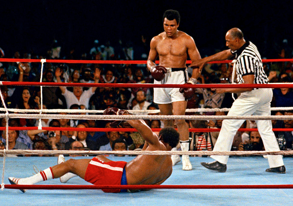 """. FILE - In this Oct. 30, 1974 file photo, referee Zack Clayton, right, steps in after challenger Muhammad Ali looks on after knocking down defending heavyweight champion George Foreman in the eighth round of their championship bout in Kinshasa, Zaire. Ali regained the world heavyweight crown by knockout in the eighth round of the fight dubbed \""""Rumble in the Jungle.\"""" (AP Photo/File)"""