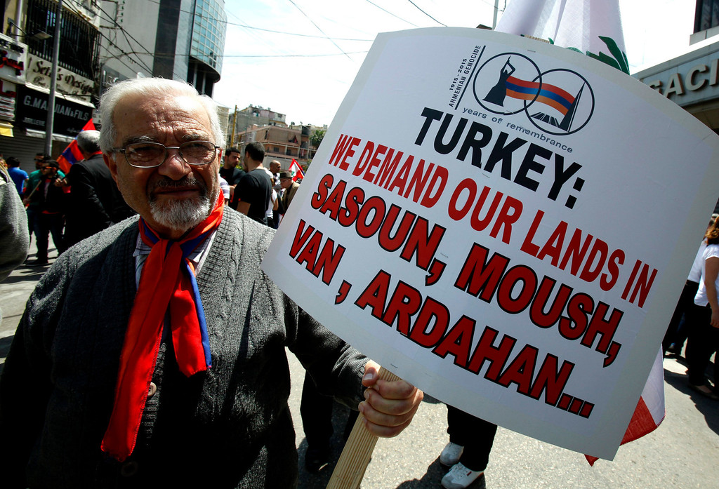 . A Lebanese man of Armenian descent holds a sign during a march from Bourj Hammoud to downtown Beirut\'s Martyrs Square, April 24, 2013, to mark the 98th anniversary of the mass killing of Armenians in the Ottoman Empire in 1915. REUTERS/Sharif Karim