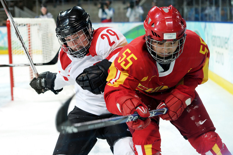 . Melanie Hafliger #29 of Switzerland and Xueting Qi #55 of China compete for the puck during the ice hockey women\'s preliminary game on day nine of the Vancouver 2010 Winter Olympics at UBC Thunderbird Arena on February 20, 2010 in Vancouver, Canada.  (Photo by Harry How/Getty Images)
