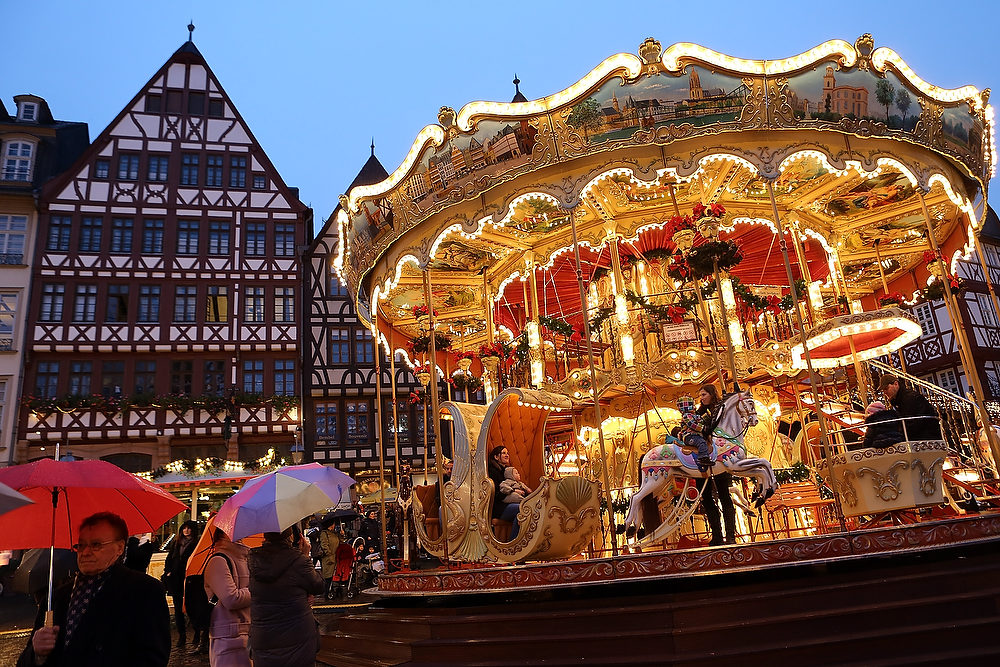 Description of . People ride a carousel at the annual Christmas market in the city center on its opening day on November 26, 2012 in Frankfurt, Germany. Christmas markets, with their stalls selling mulled wine, Christmas tree decorations and other delights, are an integral part of German Christmas tradition, and many of them opened across Germany today. (Photo by Hannelore Foerster/Getty Images)