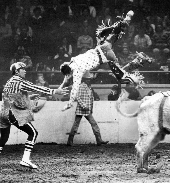 ". Lee Vogel, Stanton, Neb., is firmly aboard his mount, above, during senior boys bull-riding contest in the Little Britches. Rodeo. He bailed out, left, after riding for the full time period. Ro­deo clown Bob Donaldson reaches out to break Vo­gel\'s fall. The night competition in the Denver Coliseum was part of EQUUS, the ""Western World Fair\"" at the Na­tional Western Stock Show complex. Some of the top \'Little Britches cowboys and cowgirls from throughout the nation are competing in the rodeo. 1977. Lyn Alweis, The Denver Post  Credit: Denver Post Photo"