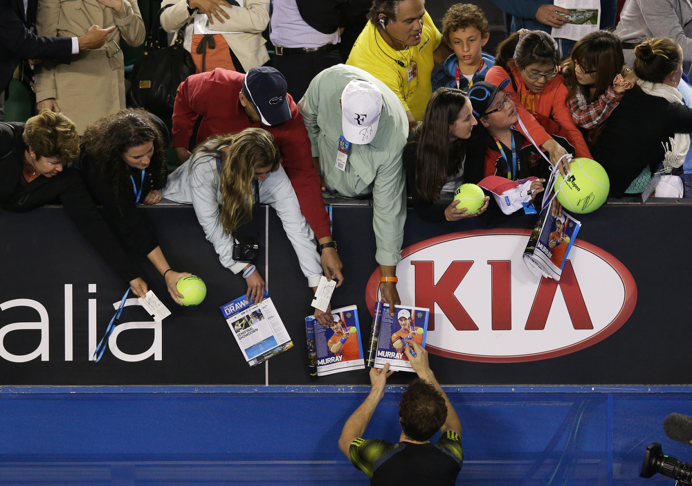 Description of . Britain's Andy Murray signs autographs after winning his semifinal match against Switzerland's Roger Federer at the Australian Open tennis championship in Melbourne, Australia, Friday, Jan. 25, 2013. (AP Photo/Aaron Favila)