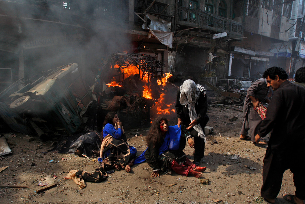 . Pakistani men reach to help injured women at the site of a blast shortly after a car explosion in Peshawar, Pakistan, Sunday, Sept. 29, 2013.  (AP Photo/Mohammad Sajjad)