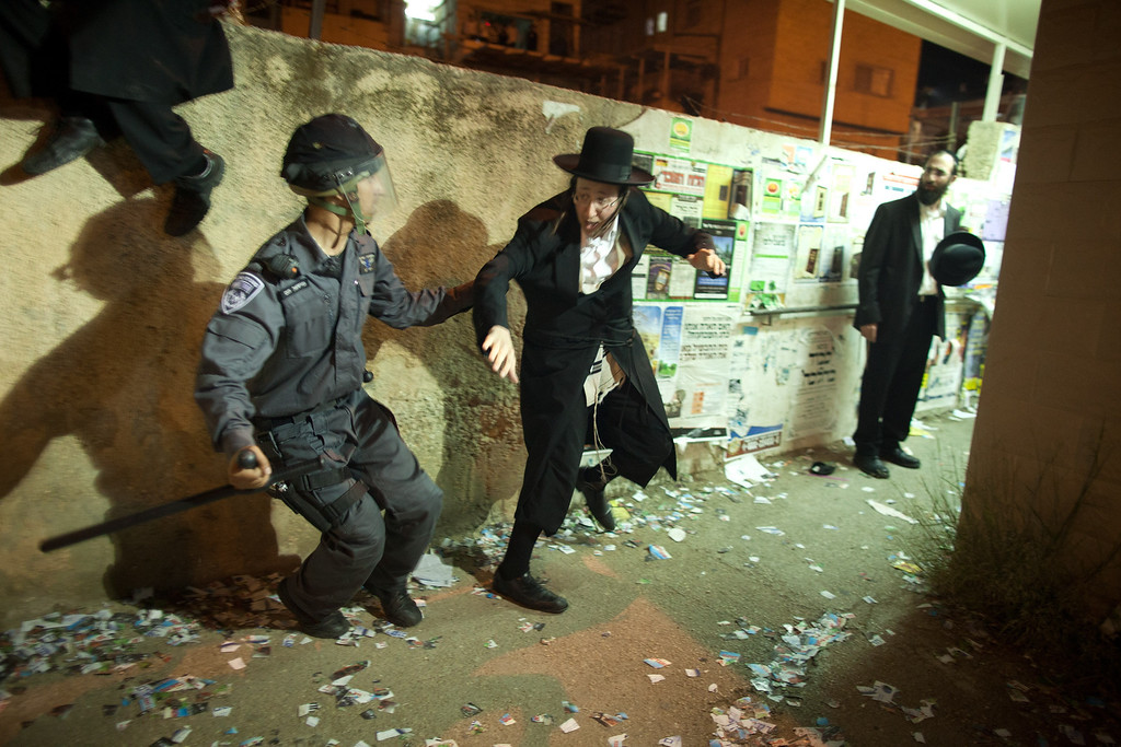 . JERUSALEM, ISRAEL - MAY 16:  Israeli riot police arrest an ultra-Orthodox demonstrator on May 16, 2013 in Jerusalem, Israel. Tens of Thousands of ultra-Orthodox Israelis have clashed with police after gathering to protest against newly proposed government legislation that would see them drafted into the military.  (Photo by Uriel Sinai/Getty Images)