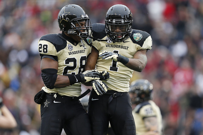. Kenny Ladler #1 and Karl Butler #28 of the Vanderbilt Commodores celebrate after Ladler\'s interception against the North Carolina State Wolfpack during the Franklin American Mortgage Music City Bowl at LP Field on December 31, 2012 in Nashville, Tennessee. (Photo by Joe Robbins/Getty Images)