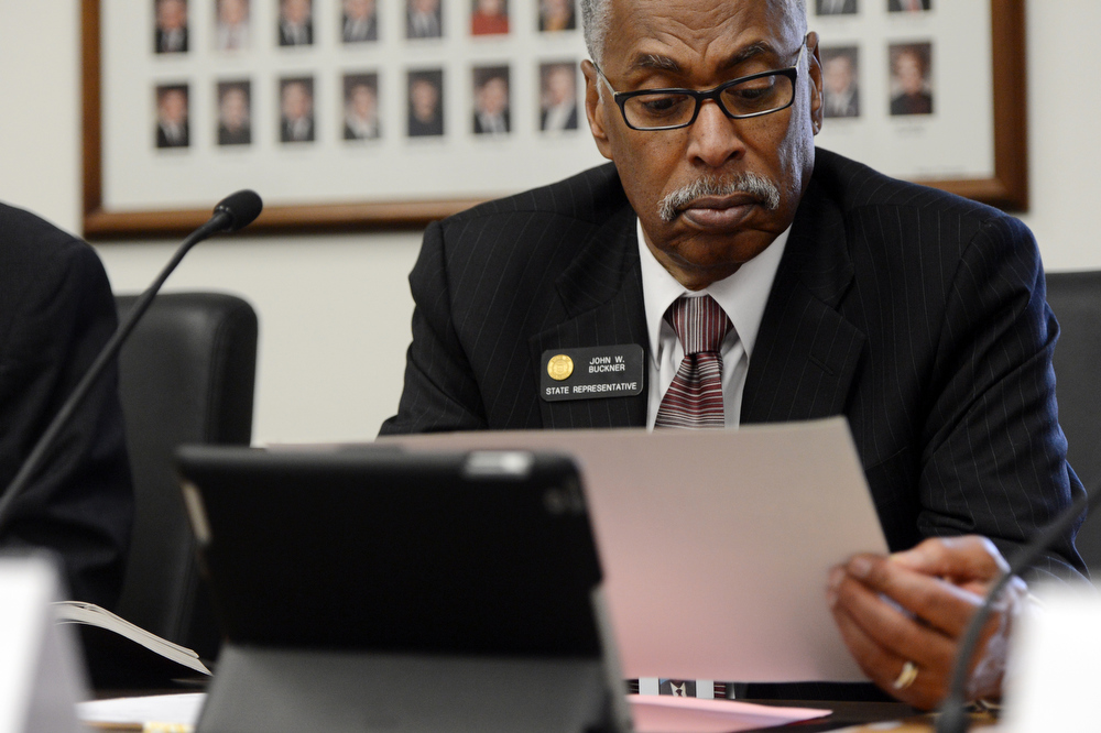 . Representative John Buckner examines a photograph of Scott Appel\'s home, that was destroyed in the Lower North Fork fire, during a House Judiciary Committee hearing on Senate Bill 23 in Denver, CO March 14, 2013. Appel\'s wife, Ann, is one of three people that died in the fire that destroyed 27 homes in Jefferson County. The Colorado House Judiciary Committee voted unanimously  to raise the amounts the state can be held liable for  under the Colorado Governmental Immunity Act. (Photo By Craig F. Walker/The Denver Post)