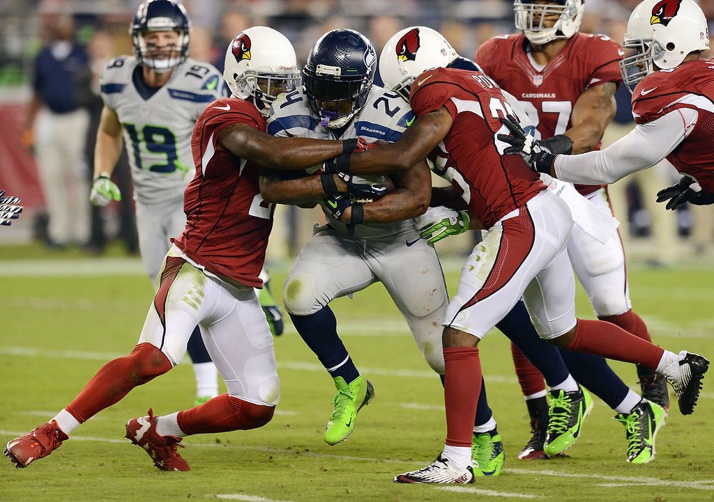 . GLENDALE, AZ - OCTOBER 17:  Marshawn Lynch #24 of the Seattle Seahawks runs through the tackles of Patrick Peterson #21 and Jerraud Powers #25 of the Arizona Cardinals at University of Phoenix Stadium on October 17, 2013 in Glendale, Arizona.  (Photo by Norm Hall/Getty Images)