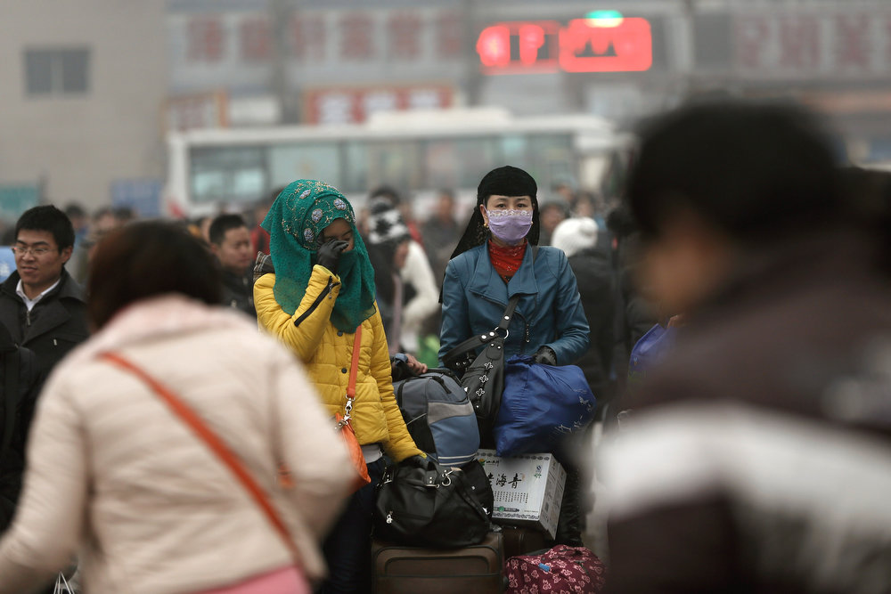 . Chinese people wearing face masks prepare to travel at the Beijing Railway Station on January 31, 2013 in Beijing, China. The Spring Festival travel season runs from January 26 to March 6 and according to reports road passenger transport in China is estimated at 3.1 billion people during this time of year.  (Photo by Lintao Zhang/Getty Images)