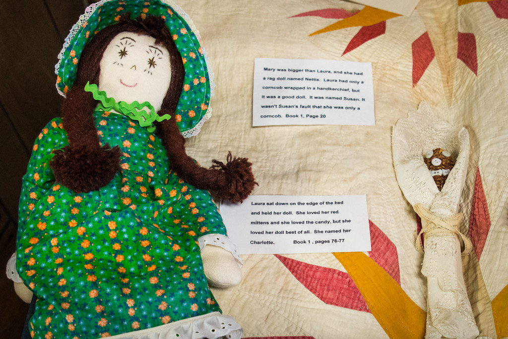 Two children's dolls like those Laura had as a small child. One is a rag doll, and the other is made of a corn cob.