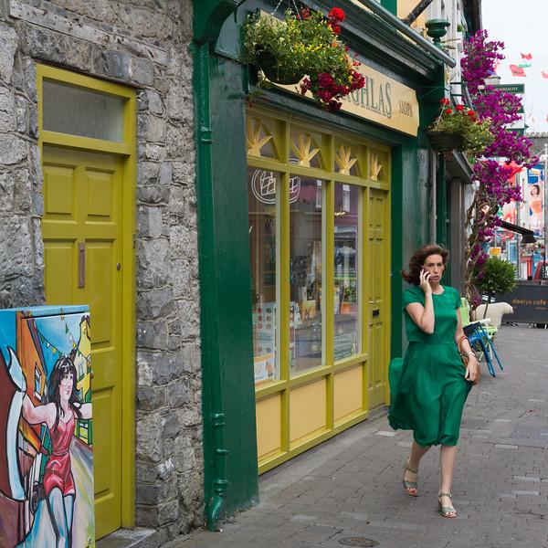 Brunette in green dress on sidewalk, Galway City, County Galway, Republic of Ireland
