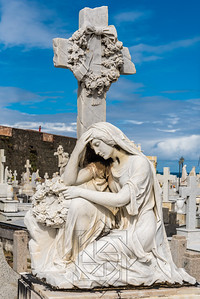 Statue of woman kneeling at grave