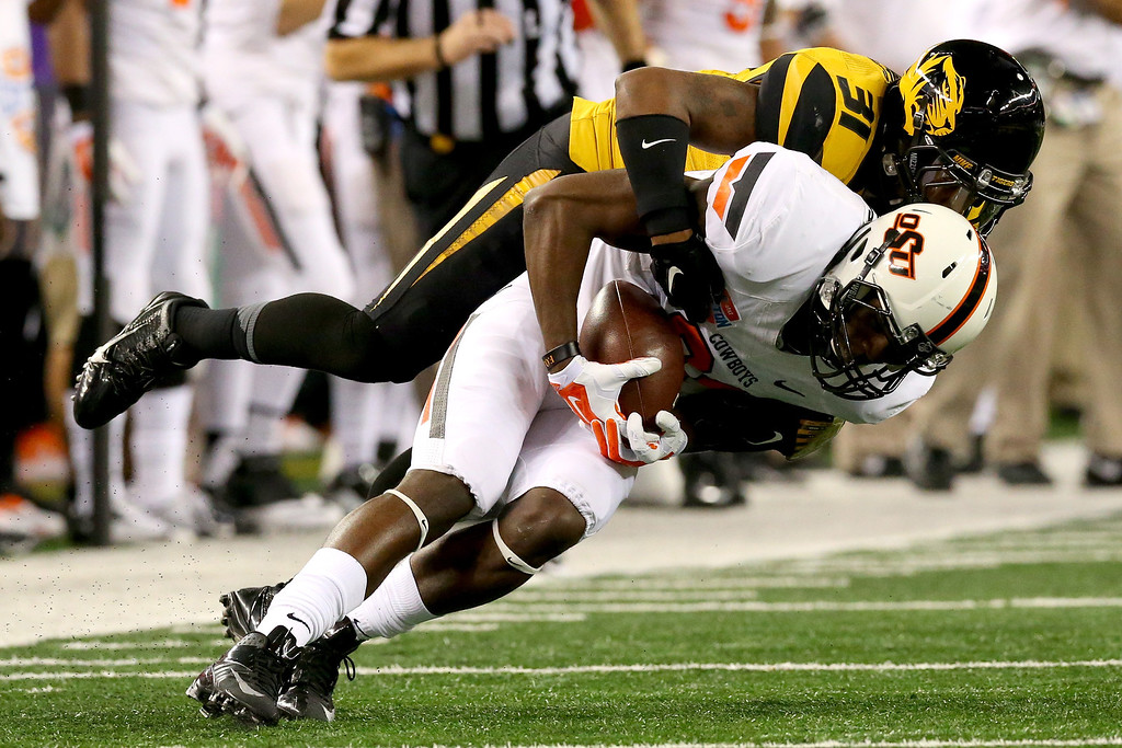 . ARLINGTON, TX - JANUARY 03:  Jhajuan Seales #81 of the Oklahoma State Cowboys makes a catch against E.J. Gaines #31 of the Missouri Tigers in the second quarter during the AT&T Cotton Bowl on January 3, 2014 in Arlington, Texas.  (Photo by Ronald Martinez/Getty Images)