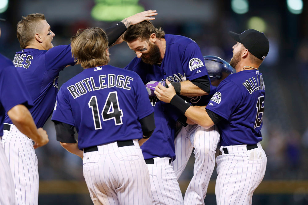 . Colorado Rockies\' Charlie Blackmon, second from right, is swarmed by teammates, from left, Brandon Barnes, left, Josh Rutledge (14) and Jackson Williams, right, after Blackmon\'s walkoff, RBI-single against the San Francisco Giants in the ninth inning of the Rockies\' 10-9 victory in a baseball game in Denver on Monday, Sept. 1, 2014.  Rockies Charlie Culberson is obscured between Rutledge and Blackmon. (AP Photo/David Zalubowski)