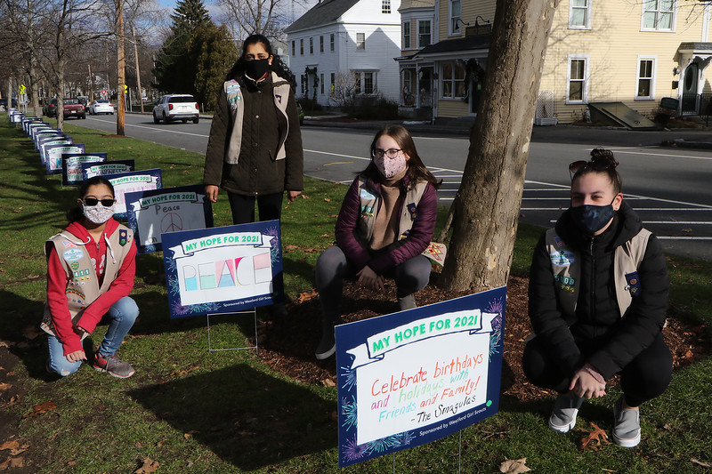 Westford Girl Scout Troop 85009's Signs of Hope project asked community members to sponsor signs on which they wrote their hopes for 2021. The 90 signs are displayed around Westford Town Common until New Year's Day, when the sponsors can come and take their signs home. From left, Anamika Pusalkar, 15, Rohita Krishnakumar, Jordyn Brooks, 13, and her sister Sydney Brooks, 16, all of Westford.  (SUN/Julia Malakie)