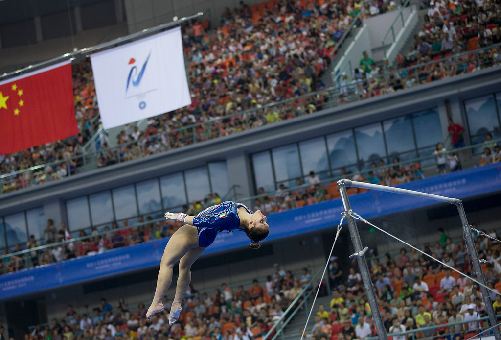 . Italy\'s Erika Fasana leaps from the uneven bars as she competes in the women\'s qualifying round of the Artistic Gymnastics World Championships at the Guangxi Gymnasium in Nanning, capital of southwest China\'s Guangxi Zhuang Autonomous Region Monday, Oct. 6, 2014. (AP Photo/Andy Wong)