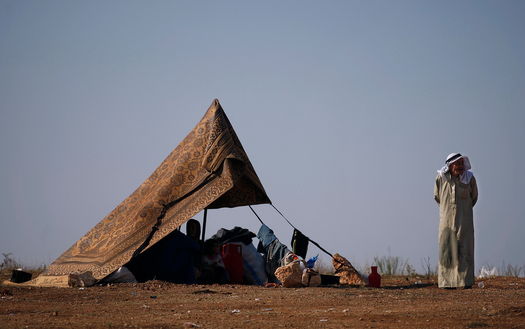 . FILE - A Syrian family who fled from the violence in their village, sit in a tent at a displaced camp, in the Syrian village of Atma, near the Turkish border with Syria, Monday, Nov. 5, 2012. (AP Photo/ Khalil Hamra, File)