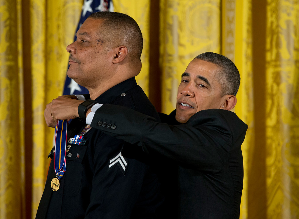 . President Barack Obama reaches up to present Los Angeles Police Department Officer Donald Thompson with the Medal of Valor during a ceremony in the East Room of the White House in Washington, Monday, May 16, 2016. The Medal of Valor is awarded to public safety officers who have exhibited exceptional courage, regardless of personal safety, in the attempt to save or protect others from harm. (AP Photo/Carolyn Kaster)