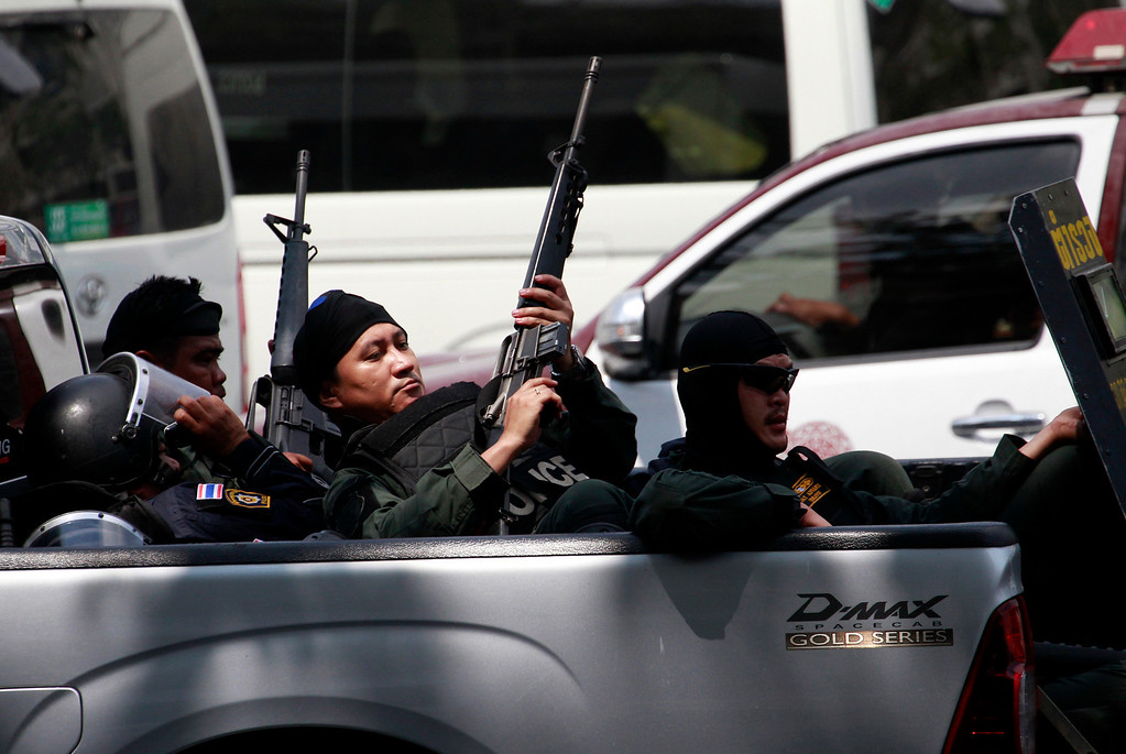 . Thai policemen check their rifles while retreating during a clash between police force and anti-government protesters Tuesday, Feb. 18, 2014 in Bangkok, Thailand.  (AP Photo/Wason Wanichakorn)