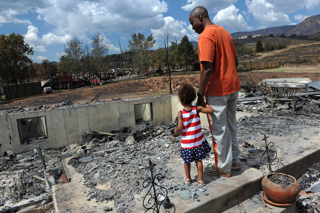 . Grace Mgana, 2, holds the hand of her father Immanuel, right, as the two survey what is left of their home. They are standing on what was the front porch leading into the family\'s home. Immanuel had been deployed in the army in East Africa and saw a picture of his burning home on the cover of the Denver Post. He was immediately allowed to come home to his wife and three children. Residents were allowed back on July 1, 2012 to the Mountain Shadows subdivision five days after the Waldo Canyon fire ravaged their neighborhood. Over 340 homes were lost in this subdivision. Helen H. Richardson, The Denver Post