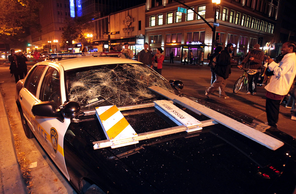 . A BART police vehicle is vandalized during a protest after George Zimmerman was found not guilty in the 2012 shooting death of teenager Trayvon Martin, early Sunday, July 14, 2013, in Oakland, Calif. Protesters angered by the acquittal Zimmerman held largely peaceful demonstrations in three California cities, but broke windows and started small street fires Oakland, police said. (AP Photo/Bay Area News Group, Anda Chu)