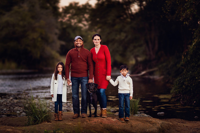 Sacramento family photographer during outdoor portrait session. Family session with a dog by a river..