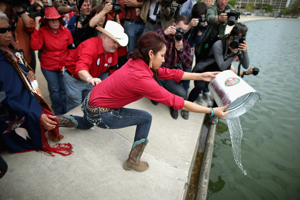 ". Nineteen-year-old Gianna Strong of the Sisseton-Wahpeton Tribe in Morton, Minnesota, pours water into the U.S. Captiol Reflecting Pool during a ceremony to demonstration against the proposed Keystone XL pipeline at the U.S. Capitol Reflecting Pool on the National Mall April 22, 2014 in Washington, DC. As part of its ""Reject and Protect\"" protest, the Cowboy and Indian Alliance is organizing a weeklong series of actions by farmers, ranchers and tribes to show their opposition to the pipeline.  (Photo by Chip Somodevilla/Getty Images)"