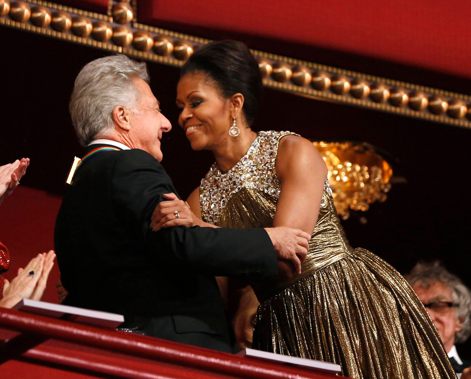 . U.S. first lady Michelle Obama (R) embraces 2012 Kennedy Center honoree, actor Dustin Hoffman at the Kennedy Center in Washington, December 2, 2012.     REUTERS/Jason Reed
