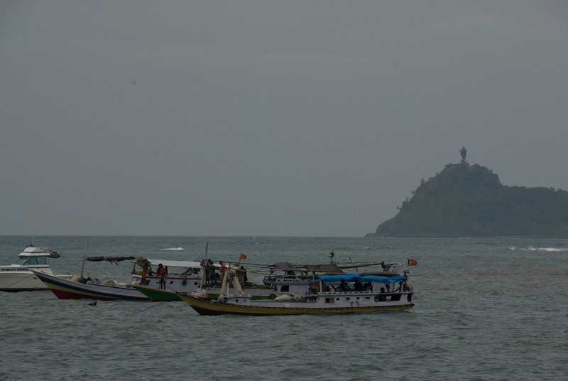 Fishermen on boats at a sea in Dili with Jesus statue atop a hill on the background.