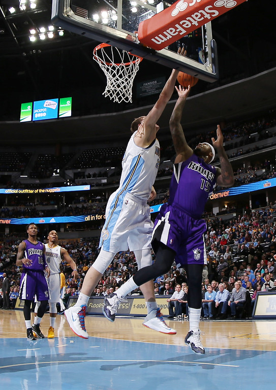 . Sacramento Kings center DeMarcus Cousins, right, shoots as Denver Nuggets center Timofey Mozgov, of Russia, covers in the first quarter of an NBA basketball game in Denver on Sunday, Feb. 23, 2014. (AP Photo/David Zalubowski)