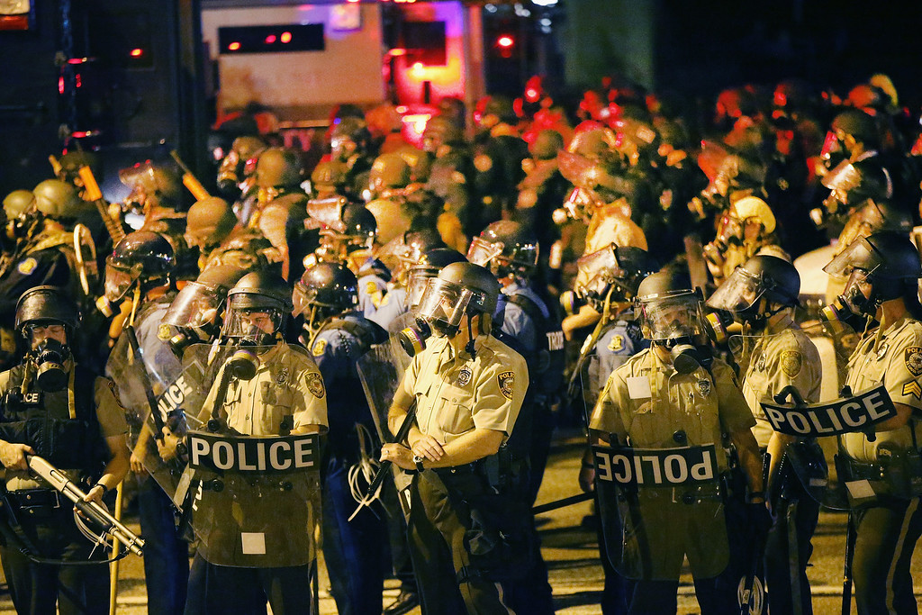 . Police advance on demonstrators protesting the killing of teenager Michael Brown on August 17, 2014 in Ferguson, Missouri. Police shot smoke and tear gas into the crowd of several hundred as they advanced near the police command center which has been set up in a shopping mall parking lot. Brown was shot and killed by a Ferguson police officer on August 9. Despite the Brown family\'s continued call for peaceful demonstrations, violent protests have erupted nearly every night in Ferguson since his death.  (Photo by Scott Olson/Getty Images)