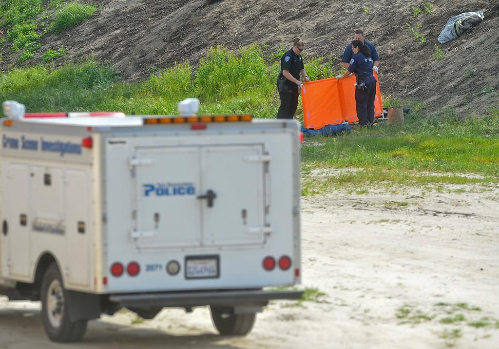 . San Bernardino police investigate the scene where the body of a woman was found near the corner of Fairway Drive and E Street in San Bernardino on Monday, Mar. 4, 2013. (Rachel Luna / Staff Photographer)