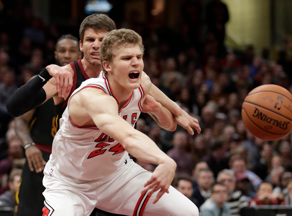 . Cleveland Cavaliers\' Kyle Korver, back, defends as Chicago Bulls\' Lauri Markkanen, from Finland, tries to pass the ball during the second half of an NBA basketball game Thursday, Dec. 21, 2017, in Cleveland. The Cavaliers won 115-112. (AP Photo/Tony Dejak)