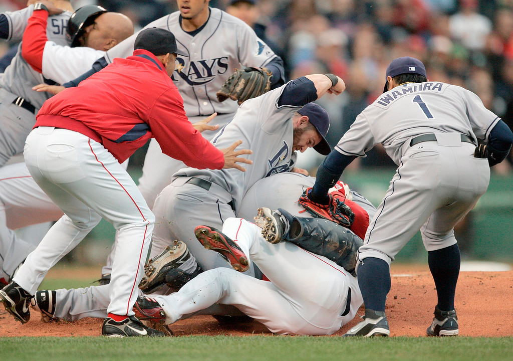 . Tampa Bay Rays\' Jonny Gomes, center, raises his fist to hit Boston Red Sox\'s Coco Crisp who lies on the ground beneath Rays catcher Dioner Navarro in the second inning of a baseball game, Thursday, June 5, 2008, in Boston. Tampa Bay Rays\' Akinori Iwamura, of Japan, is on the right. Crisp was hit by a pitch and charged the mound which resulted in a bench clearing brawl. (AP Photo/Michael Dwyer)