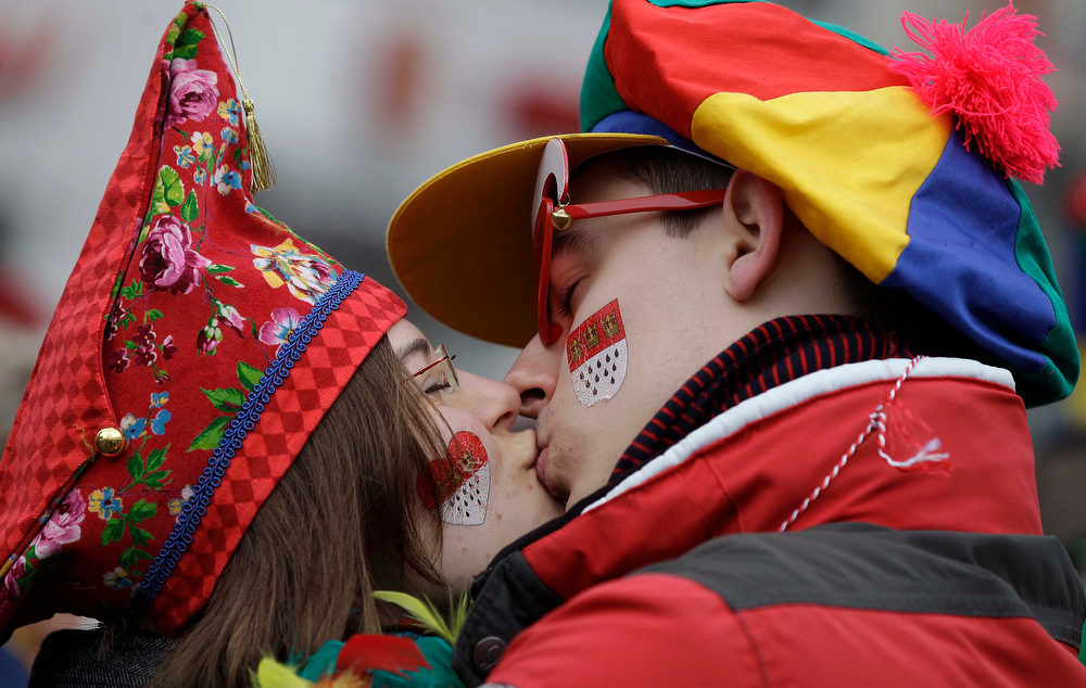 """Description of . Carnival revellers kiss each other, as they celebrate the start  of the street-carnival with its tradition of fools entering the town halls and women cutting off men\'s ties with scissors on carnival\'s so called \""""Old Women\'s Day\"""" in Cologne, Germany, Thursday, Feb. 7, 2013. The \""""Old Women\'s  Day\""""  is traditionally the beginning of  street carnival, the foolish street spectacles in the carnival centers of Duesseldorf, Mainz and Cologne. (AP Photo/Frank Augstein)"""