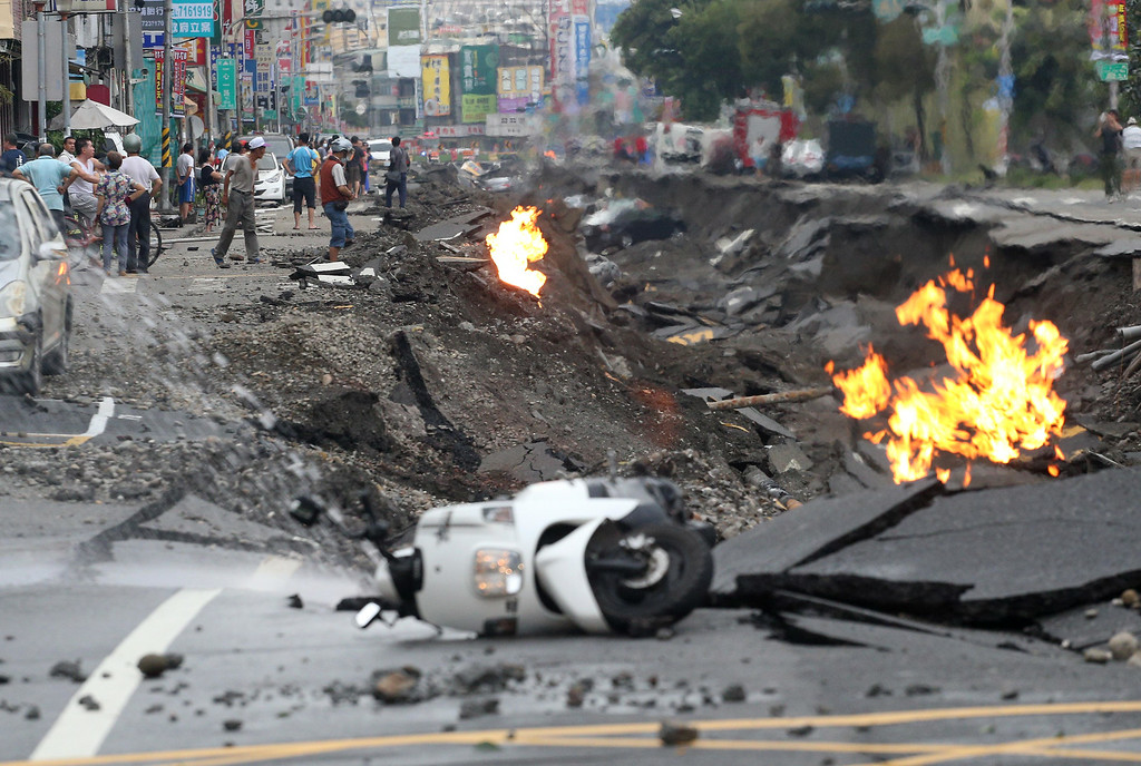 . Vehicles are left lying on a destroyed street as part of the street is burning with flame following multiple explosions from an underground gas leak in Kaohsiung, Taiwan, early Friday, Aug. 1, 2014. Several underground gas explosions ripped through Taiwan\'s second-largest city overnight, hurling concrete through the air and blasting long trenches in the streets, authorities said Friday. (AP Photo)