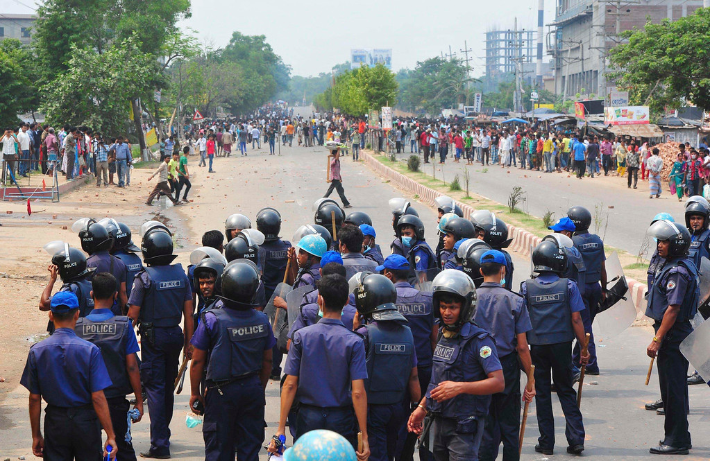 . Policemen stand guard as garment workers block a street demanding the arrest of those responsible for the collapse of the Rana Plaza building in Savar, 30 km (19 miles) outside Dhaka April 26, 2013. Two factory bosses and two engineers were detained in Bangladesh on Saturday, three days after the collapse of a building where low-cost garments were made for Western brands killed at least 352 people. More were being pulled alive from the rubble at the building, where police said as many as 900 people were still missing in Bangladesh\'s worst ever industrial accident.  REUTERS/Stringer