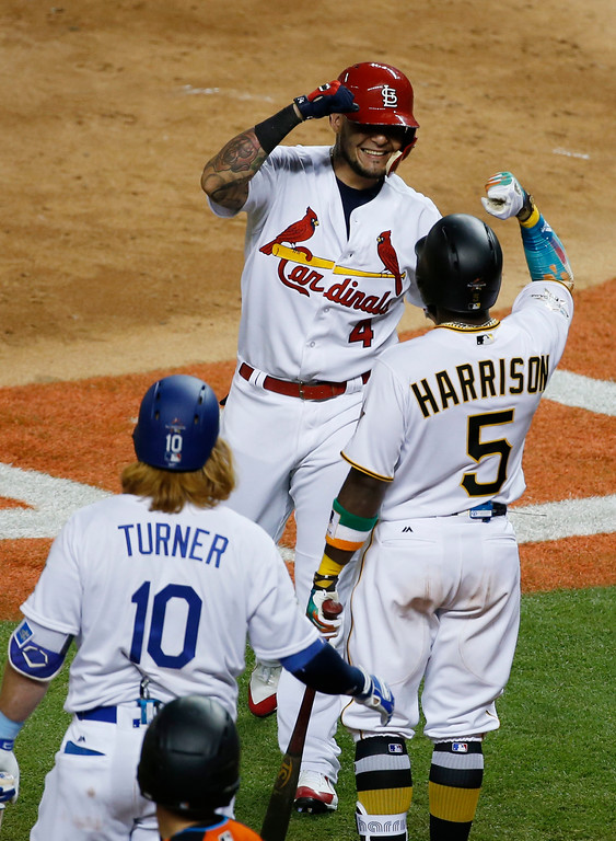 . National League\'s St. Louis Cardinals catcher Yadier Molina (4), is congratulated by Pittsburgh Pirates Josh Harrison (5) and Los Angeles Dodgers Justin Turner (10), after hitting a homerun in the sixth inning, during the MLB baseball All-Star Game, Tuesday, July 11, 2017, in Miami. (AP Photo/Wilfredo Lee)