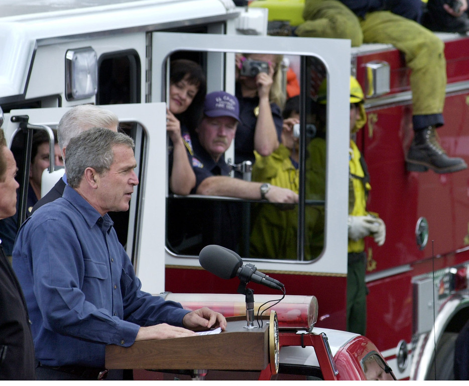 . President Bush addresses firefighters at the California Department of Forestry base camp at Gillespie field in El Cajon, Calif., Tuesday, Nov. 4, 2003. He had just toured the damage from the Cedar Fire, the biggest fire in California\'s history.  In the window of the firetruck in back are, El Cajon Fire Department engineer Walt Jones and public information officer Monica Zech, left. (AP Photo/John Gibbins, San Diego Union-Tribune/Pool)